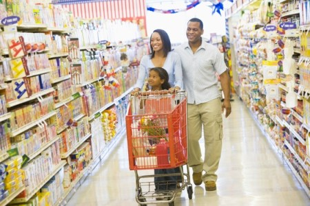 A young couple and their daughter grocery shopping in the mall during Christmas season