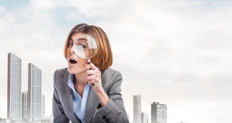 mujer de negocios busca con lupa agente inmobiliario eficiente