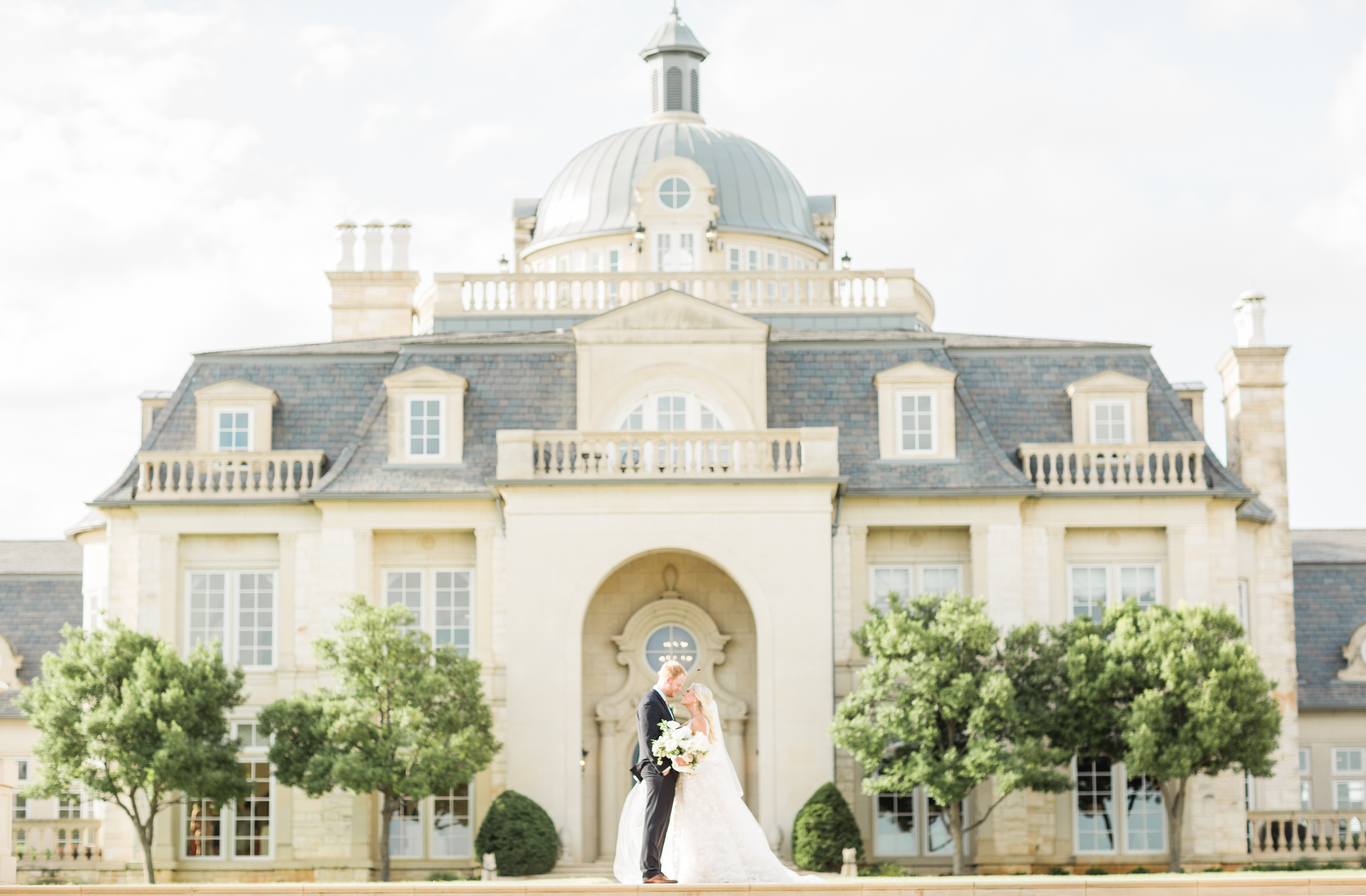 Exterior of the Olana Wedding Venue in Dallas, couple stands centered for their wedding day. Green trees surround venue.