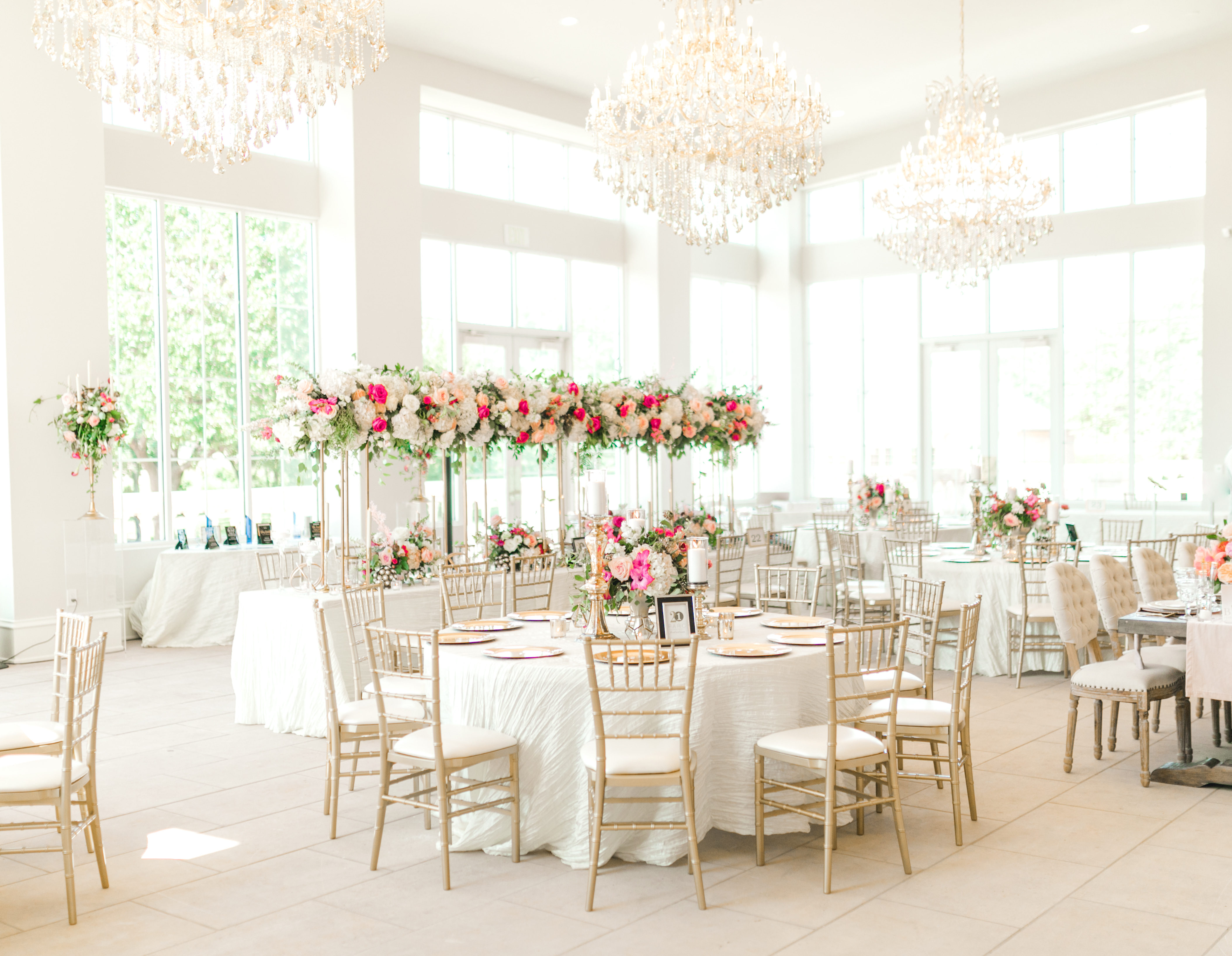 Interior of The Olana Dallas Wedding Venue, white tablecloths, giant floral arrangements and pretty chandeliers.