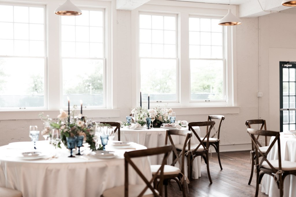 Interior of School House, Dallas Wedding Venue. White walls and table cloths, dark wood chairs, very open concept.