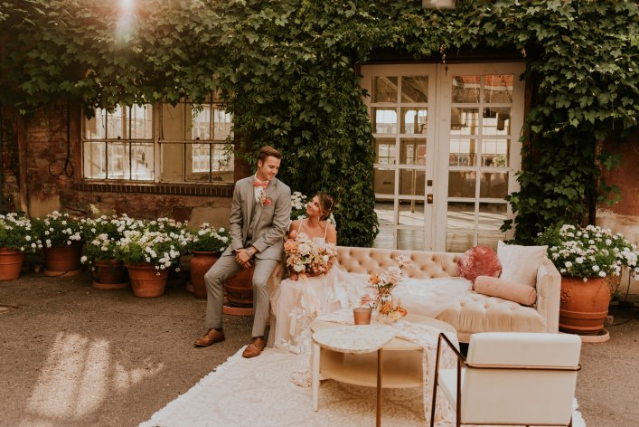 Couple at Blanc Venue, Colorado. Surrounded by white furniture, and green plants outside of the venue. Photo has golden hue, couple is smiling