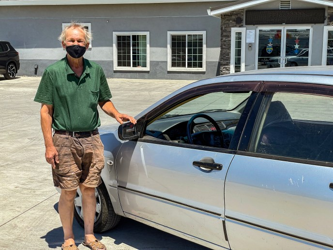Dennis Lindroos in front of his 2003 Mitsubishi Lancer ES, his first-ever brand-new car, which currently has more than 550,000 miles on it