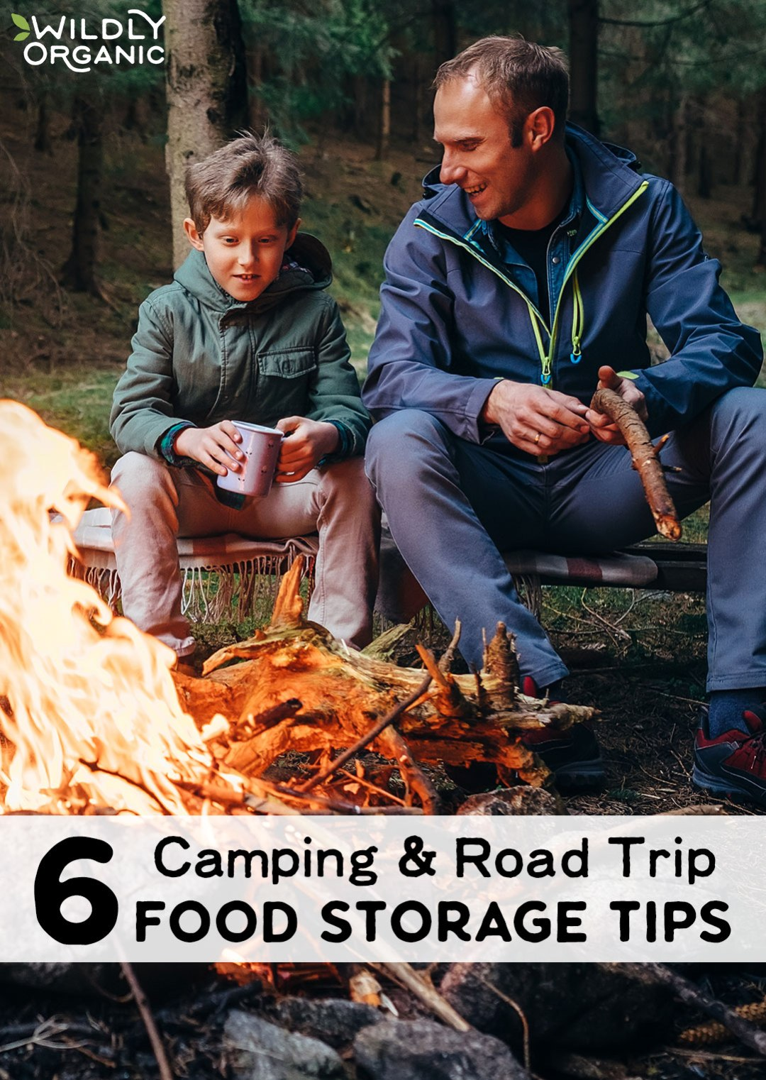 boy with his dad sitting in front of a campfire for camping and road trip food storage tips