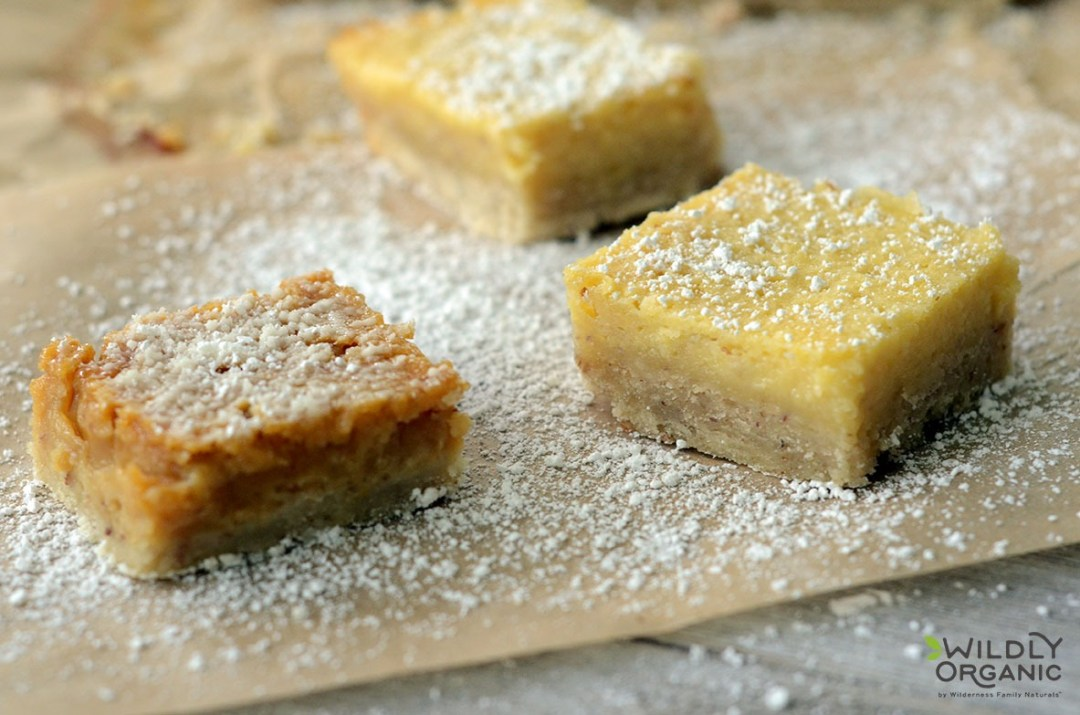 Photo of the color difference between gluten-free lemon bars made with coconut syrup or honey. Gluten-Free Lemon Bars – Tart and rich, lemon bars are the quintessential summer treat. There is nothing better than sinking your teeth into a lemon bar with a creamy, custard lemon filling and a crunchy crust. Gluten-free lemon bars are a great summer treat to bring along to any potluck - they really just make the perfect dessert to end any meal!