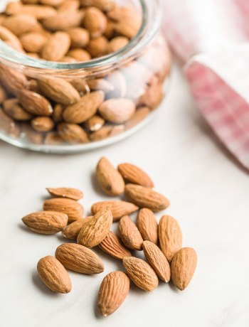 A bowl of raw almonds on a table with almonds scattered around it