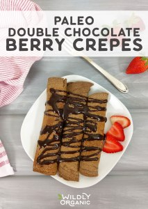 Photo of a plate of paleo double chocolate crepes from above with strawberries on the side.