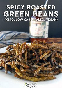 Photo of spicy roasted green beans on a plate with cooking oil in the background.