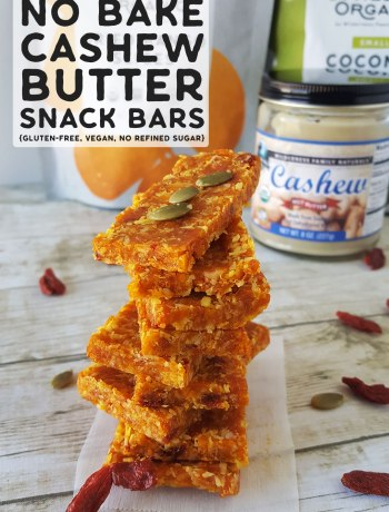Photo of stacked no bake cashew butter snack bars with a jar of cashew butter in the background.