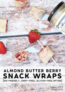 A photo of almond butter berry snack wraps with a strawberry on a wooden skewer.