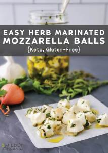 A photo of herb-marinated mozzarella bites on a plate with a jar of olive oil and herbs.
