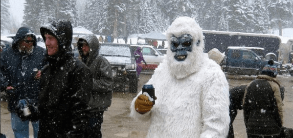 A Man in a yeti costume holds a beer in the snow in the Mary Jane Parking Lot