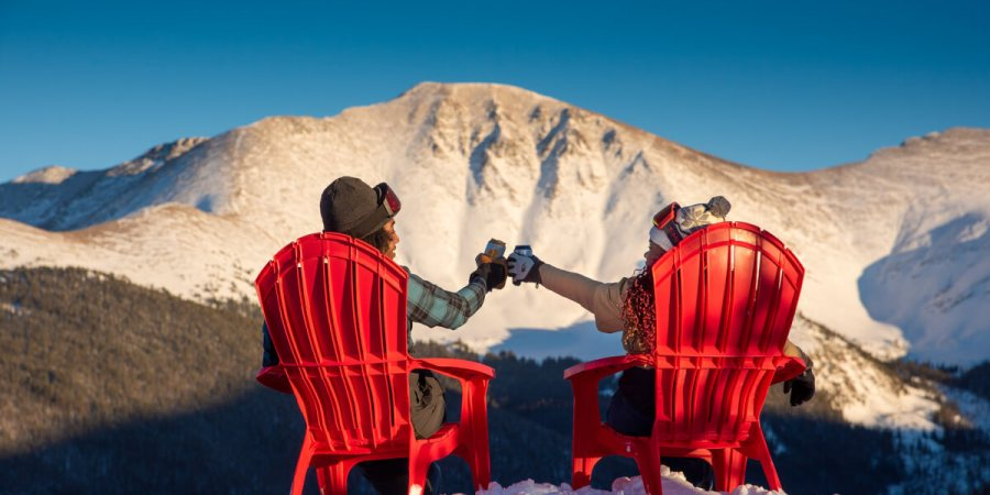 Two seated people raise a cheers in front of a snowy mountain peak.