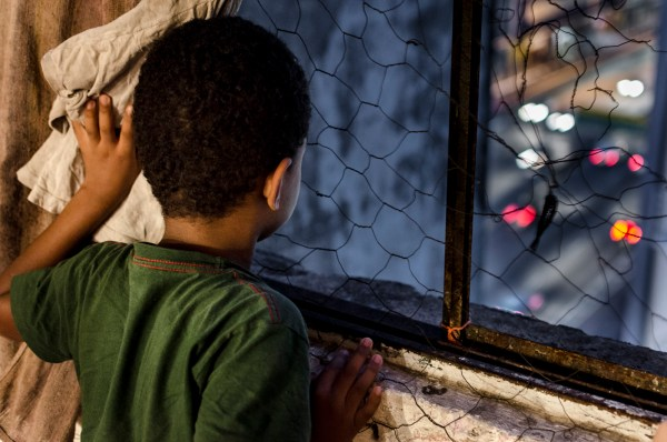 Cintia Rodgrigues Sousa's son looks out the window Prestes Maia 7th floor early in the morning. (c) Gustavo Basso/WITNESS