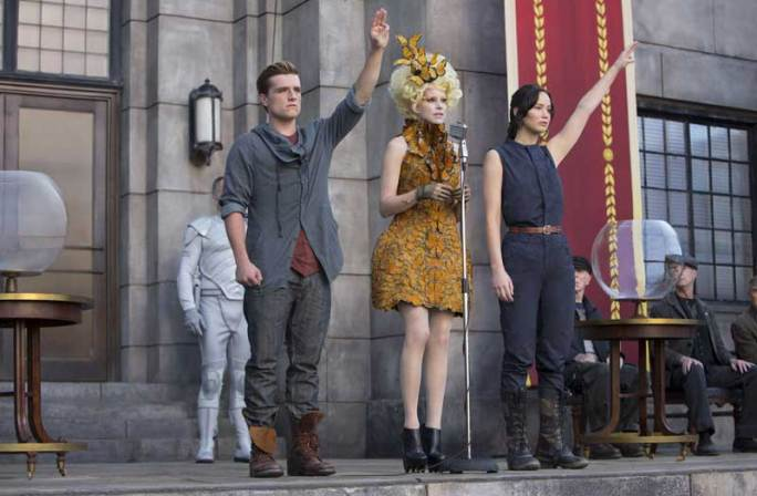 The main character Katniss and her partner Peeta show the three finger salute as they are chosen to represent their district for the Hunger Games again.