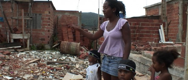 A resident tells her story amidst rubble. Photo courtesy of Jason O'Hara.
