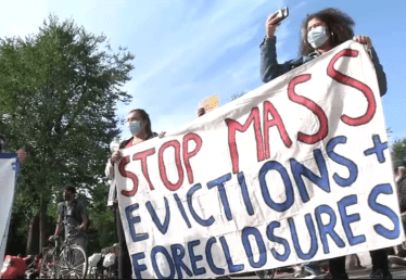 "Two people with a protest banner that says ""Stop Mass Evictions + Foreclosures"""