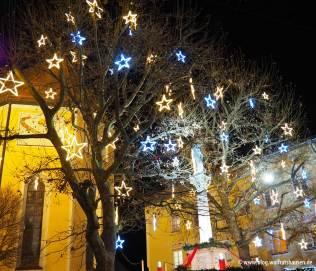 Die Mariensäule zwischen den weihnachtlich geschmückten Plantanen