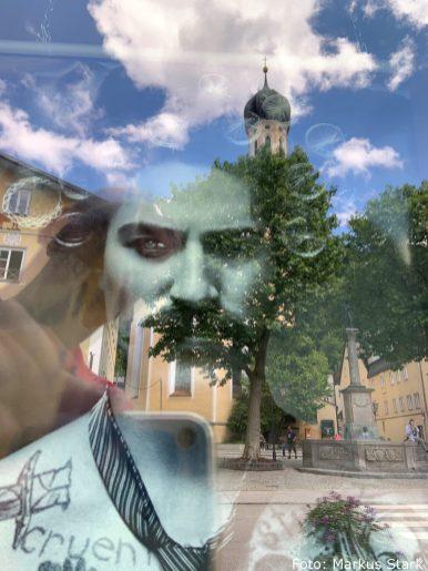 """""""Anbei ein Foto von meinem Lieblingsplatzerl und das ist eigentlich die ganze Altstadt. Auf dem Foto spiegelt sich im Schaufenster des Friseurs mit dem Lockenwickel-Mann, die Kirche, der Brunnen und der weiß-blaue Himmel - wunderschöne Zufallsszene."""""""