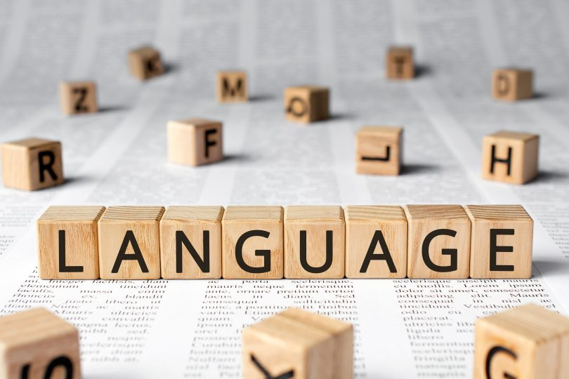 Language - word wooden blocks with letters, language learning speech concept, random letters around, paper background newspaper text