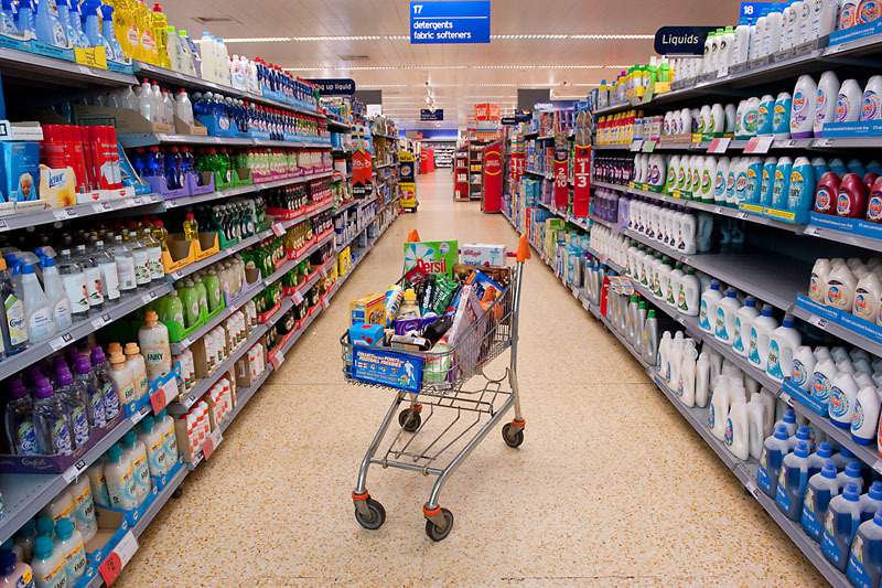 A shopping trolley containg many typical products at a supermarket in the UK. Cakes, biscuits, chocolate, confectionery, meat, frozen fish, spreads, cereals, sweets, cosmetics, crisps, snacks, cleaning and hygene products amongst the items - Many products contain a surprising amount of Palm Oil.