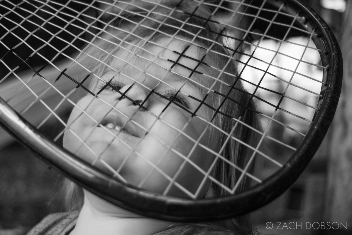 toddler with face in racket