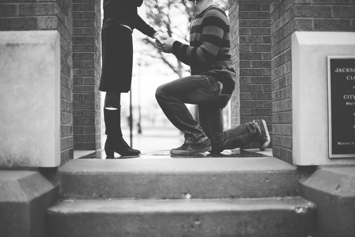 a man on his knees, proposing to his girlfriend