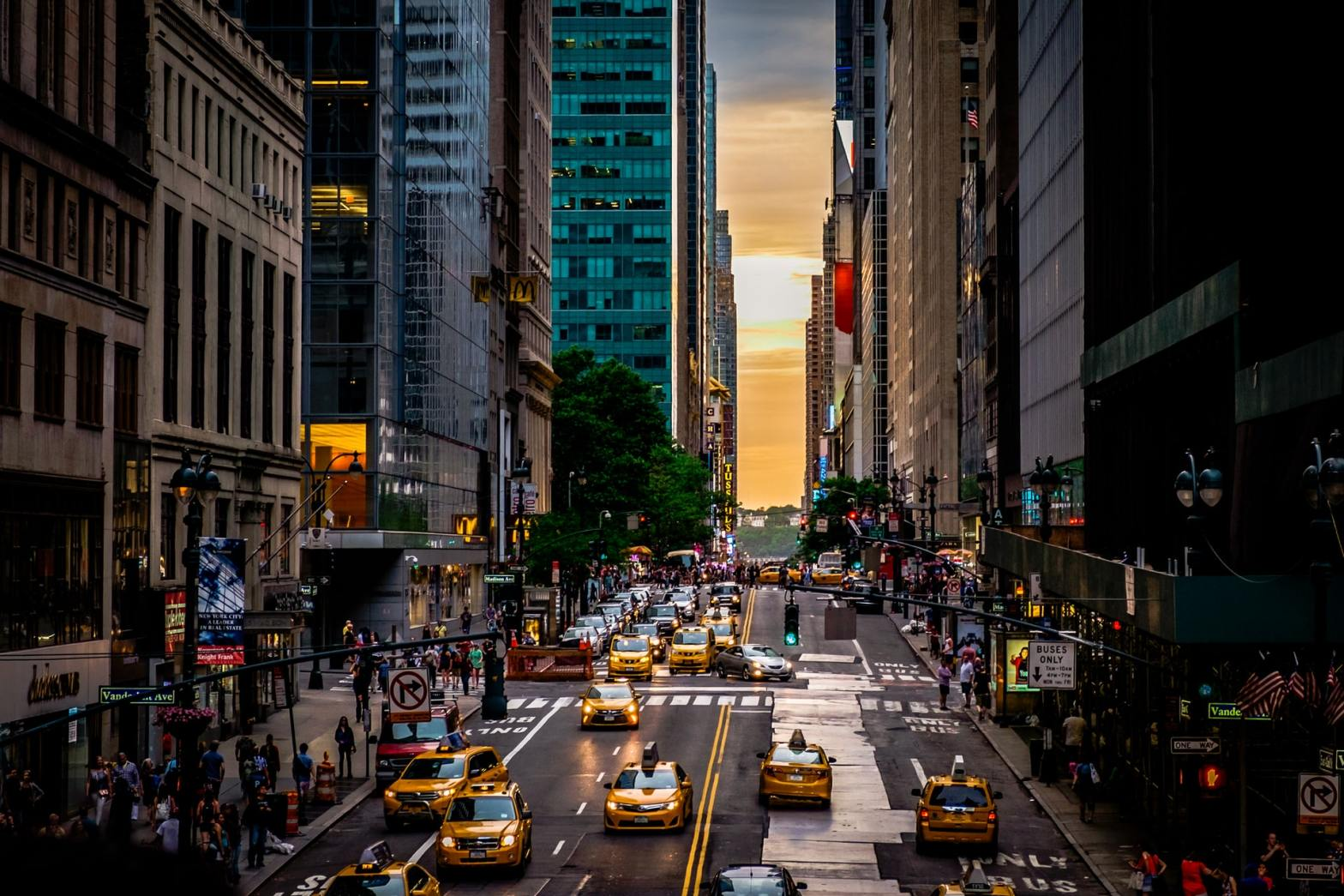 Numerous Yellow Taxi cabs and Uber cabs driving down a street in NYC