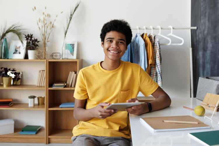 a happy teenager sitting in his room