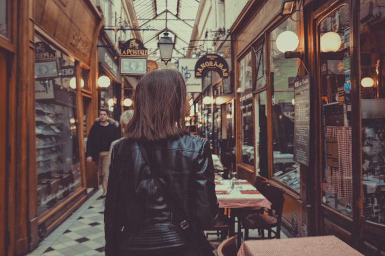 person walking through an alley with restaurants and cafes in Paris