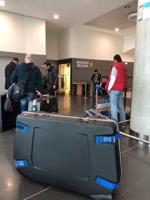 An der Sperrgepäck-Ausgabe warte ich in einer Horde hochkonzentrierter Triathleten auf meinen Koffer.