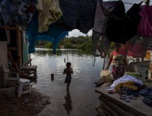 Crianças brincam em área alagada em favela do Recife