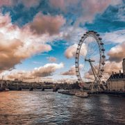 ferris wheel beside body of water under cloudy sky during daytime