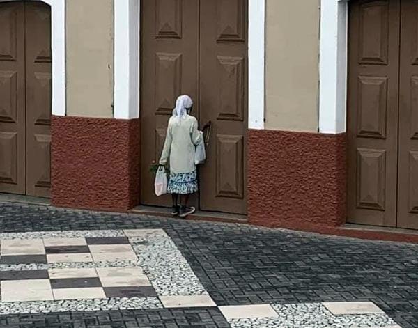 No Agreste ‒ Imagem de idosa rezando na porta de igreja fechada devido a pandemia viraliza
