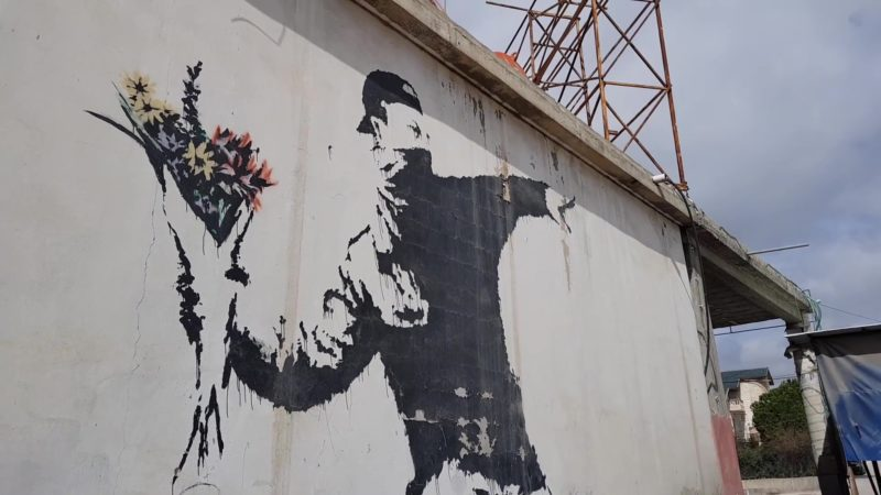 Banksy-–-Love-Is-In-The-Air-Flower-Thrower-2005-Ash-Salon-Street-Bethlehem-West-Bank--800x450