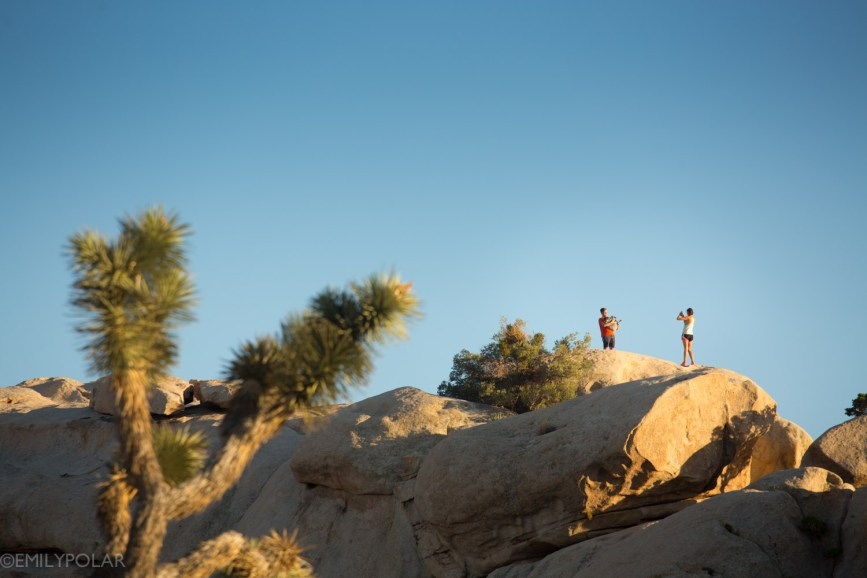 Couple hanging out on top of rock ridge at sunset in Joshua Tree National Park.