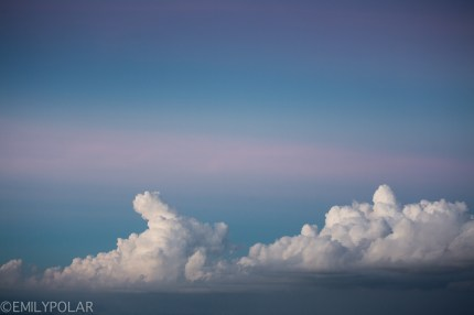 Big puffy white clouds in the blue and pink skies at sunset in Bali.