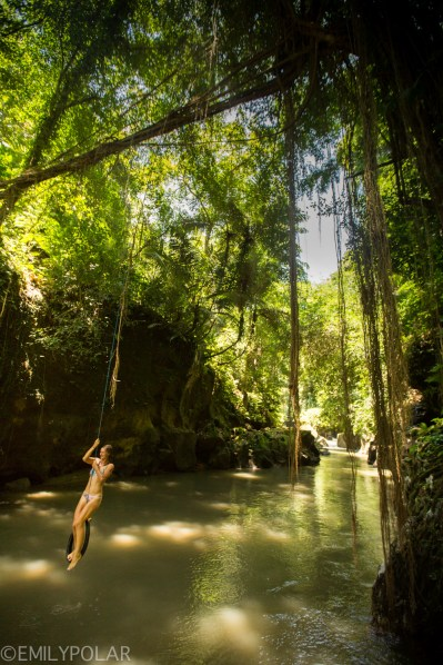 Women swimming with in lush forest river in Bali, Indonesia.