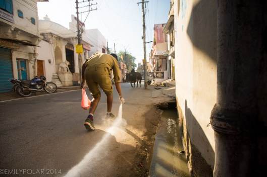 Indian boy laying a line of chalk down on the street in front of holy temple.