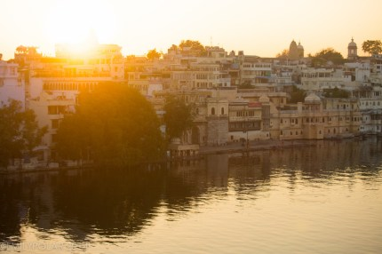 Sun rising over river and hotels in Udaipur, Rajasthan.