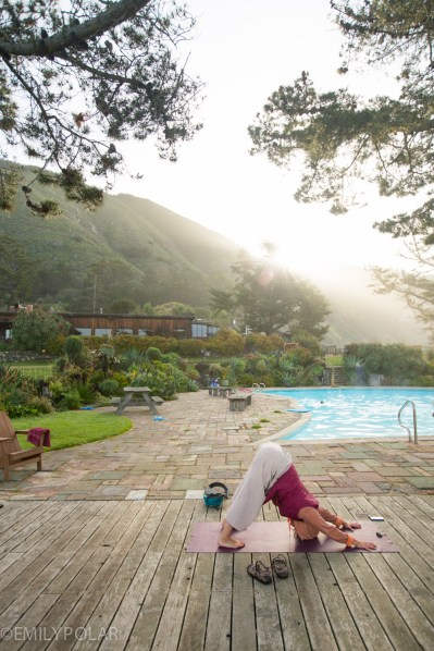 Woman practicing yoga in the morning sun by the pool at Esalen.