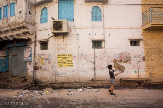 Young boy playing with cardboard on the streets in Jodhpur, India.
