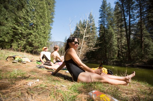Woman in black one piece swim suit with a beer and sunglasses enjoying the sun along the Merced River in Yosemite.