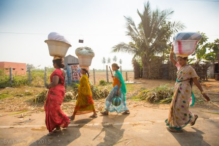 Women carrying baskets on their head while walking down the road near Hampi, India.