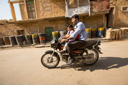 Cute young Indian girl rides on the front of the motorcycle while dad drives her to school in Jaisalmer.