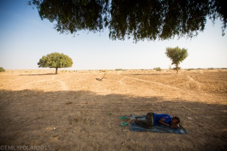 Young man laying down under a tree in the desert resting under the shade of a hot day.