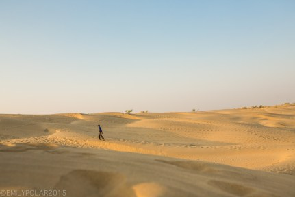 Young Rajasthani boy walking in the Thar desert alone in Rajasthan.
