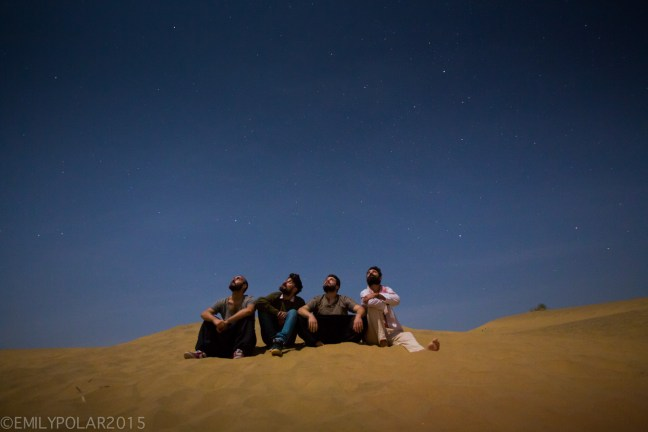 Group of Italian men sit on the desert sand at night looking up at the stars in Rajasthan.