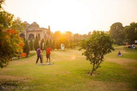 Indian boys setting up a cricket match in Lodi Gardens at sunset.