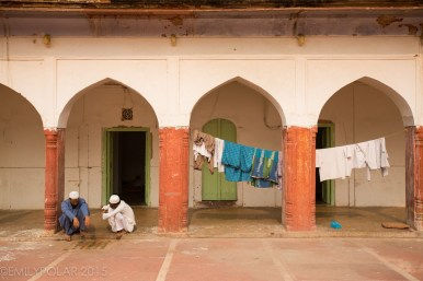 Muslim men and boys hanging out at mosque while laundry dries on the line in Old Delhi, India.
